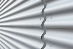 Wall cladding with corrugated panels; Modern wall covering; Corrugated sheet at industrial building; Construction elements of modern architecture