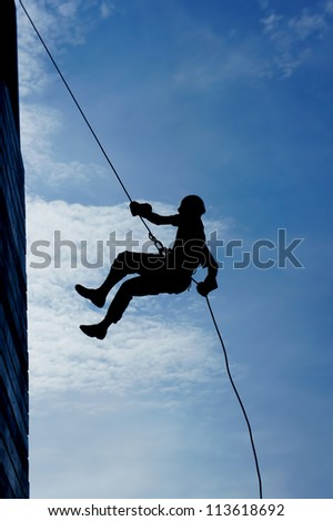 wall climber silhouette against blue sky
