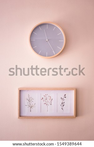 Wall clock and three pictures with flower shapes on the wall. Minimalistic concept, interior design