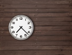 Wall clock hanging on the left side in a brown plank