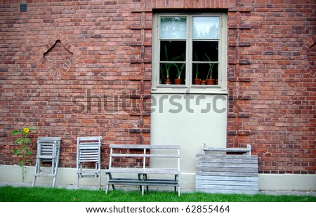 wall from a red brick, by a window a wooden garden furniture