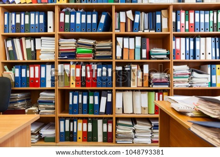 Wall from shelves with colourful file binders, interior of an office room with papers and documents