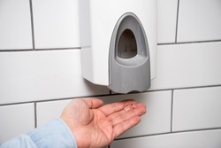 Wall hand pump sanitizer soap gel dispenser. Hand washing and good hygiene to prevent contamination from coronavirus virus and other germs.