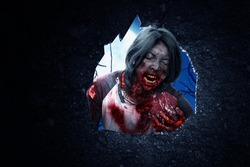 Wall hole with a scary zombie eating raw meat with the night scene background