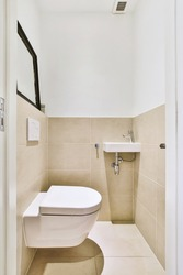 Wall hung toilet and small sink in corner in lavatory room with beige tile