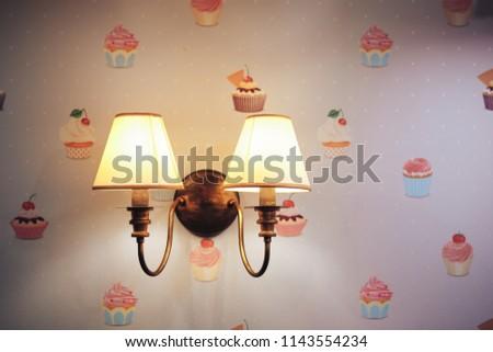 Wall lamp in the children's room. Chandelier in the children's room. Close-up. Wallpapers with cakes #1143554234