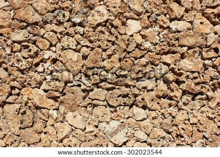wall made of natural rough stone (sandstone), different sizes of stones make up the pattern for this stone wall