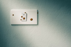 wall mounted light switch on concrete wall with virus or germ effect, people should clean it as often as possible, concept of COVID-19 spread and prevention, dramatic tone effect