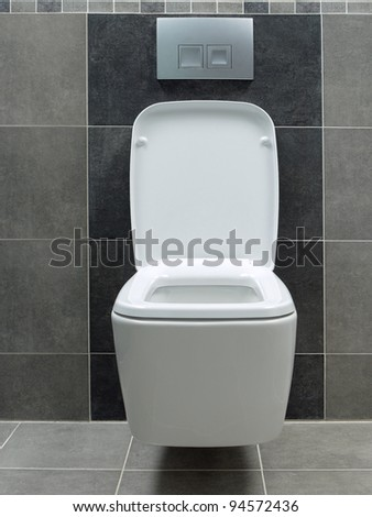 Wall mounted white ceramic toilet in gray tiled bathroom