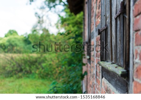 Wall of an outdoor hovel with closed, wooden windows. The focus lays on the center of the first window. Bushes and tress are in the background. #1535168846