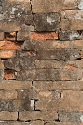 Wall of ancient and damaged orange bricks during a sunny day, covered with a thin layer of gray plaster.