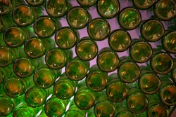 Wall of back-lit green bottles. glass background, glass texture. The texture from the bottom of the green glass