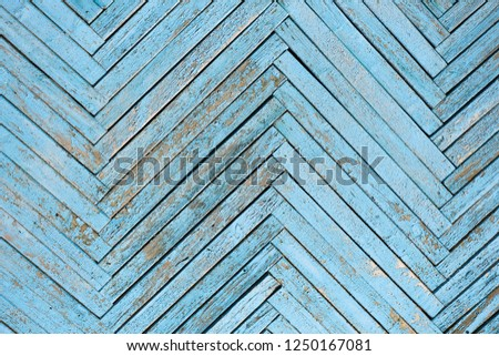 Wall of blue wooden slats. Exfoliated blue paint. Diagonal laying, zigzag line #1250167081
