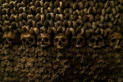 Wall of bones with a row of skulls. Skulls and bones in catacombs. Underground cemetery.