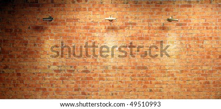 Wall of brick illuminated by three lighting equipments