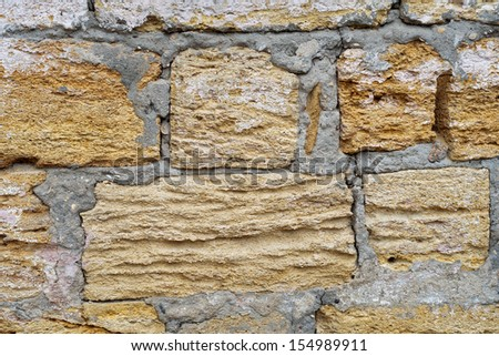 wall of limestone blocks in plaster and pits
