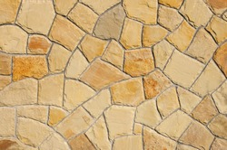 wall of natural stone in various shades of light brown sandstone/sandstone texture background/pattern formed by sandstone rocks of various shapes and colors