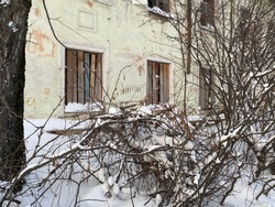 Wall of old abandoned house with boarded-up windows in disrepair. Winter season