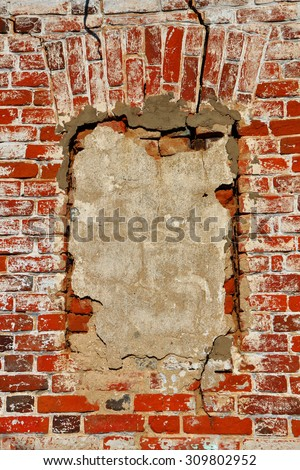 Wall of old orange shabby bricks with concreted window opening as background or texture. Vertical orientation