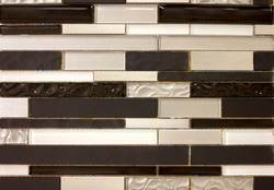 wall of small ceramic tiles, horizontal long bars of black, white and pearl color background close-up
