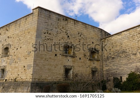 Photo of  Wall of the ancient European castle with small windows and a lot of gunshots residues. Vintage fortified structure.