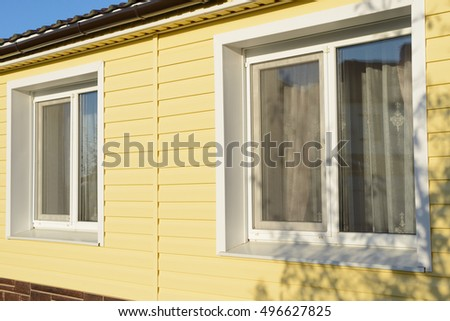 wall of the house with two windows coated with yellow siding #496627825