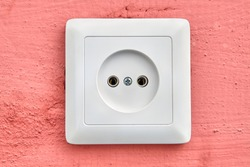 Wall outlet of European type, square-shaped, white color, close-up.