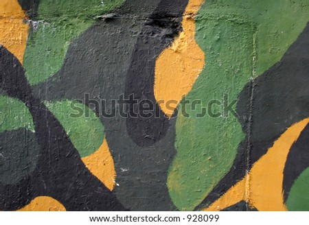 Wall painted in army camouflage colors - yellow, green and black