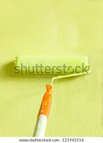 Wall painter using a paint roller, painting a wall in motion