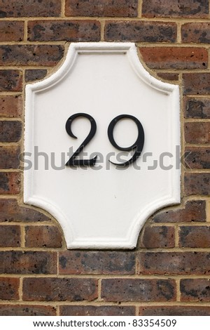 Wall plaque showing number twenty nine, 29. Outside wall of a house.