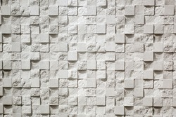 Wall plastered in the form of repeating squares mosaic, 3D texture. The gray background of decorative stucco squares. Textured Wallpaper