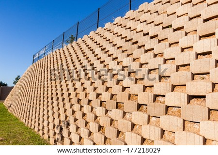 Wall retaining blocks inter locking concrete products in construction with fencing on field plateau.