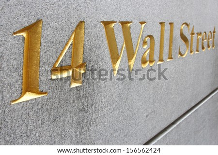 Wall street address  in golden letters embedded  on rough granite wall