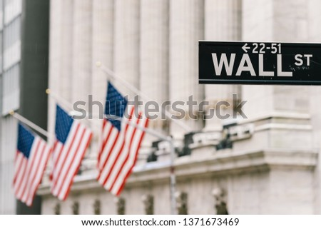 Wall Street sign post with American national flags in background. New York city financial economy district, stock market trade and exchange, or international business concept