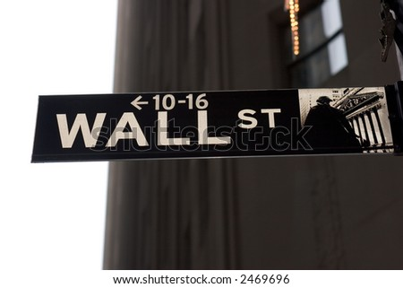 Wall Street street sign against sky and buildings