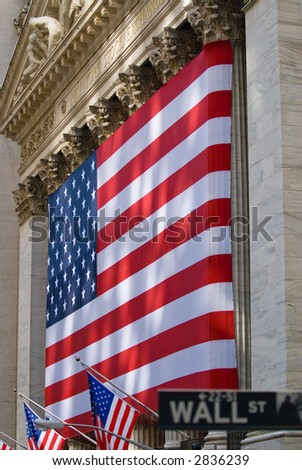 Wall Street street sign with lovely sun-dappled view of the historic New York Stock Exchange building draped in an American flag, background focus.