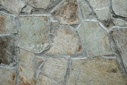 Wall texture of natural chipped stone with cement joints. Decorative stone background. Cobblestone pavement close up