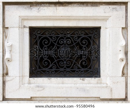 wall with a window and worn out ornamental bars.