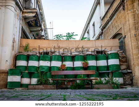 Wall with barrels and crenels marking the green line in the UN buffer zone between Greece and Turkey in Cyprus, Nicosia.