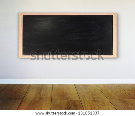 Wall with chalkboard and wooden parquet - stock photo