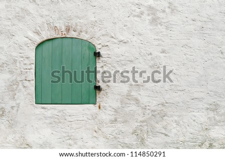 wall with closed green wooden...