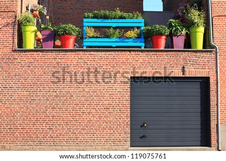 Wall with garage and brightly coloured flower pots