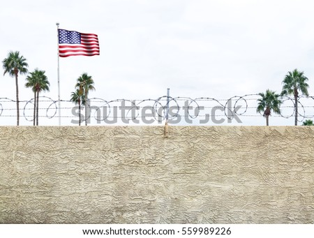 Shutterstock Wall with secure barbed wire fence along the southern border of the United States