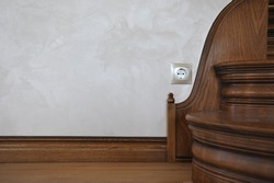 Wall with socket and part of wooden stairs.