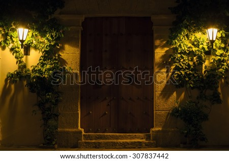 Wall with vintage massive wooden door and two lit street lamps in greenery of bushes