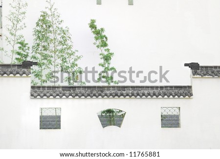 Wall with windows and bamboo.this wall with roof is familiar in chinese ancient building.