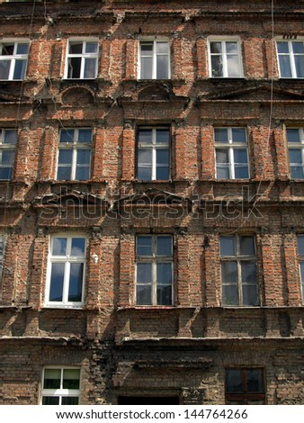 wall with windows of an old, damaged residential building in Wroclaw, Poland