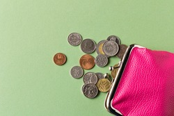 Wallet with coins on a green background. Close up. Selective focus. The concept of poverty