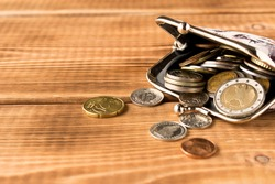 Wallet with coins on a wooden table. Close up. Selective focus. The concept of poverty