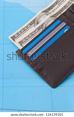 Wallet with dollars cash and credit cards on map background for travel concept.